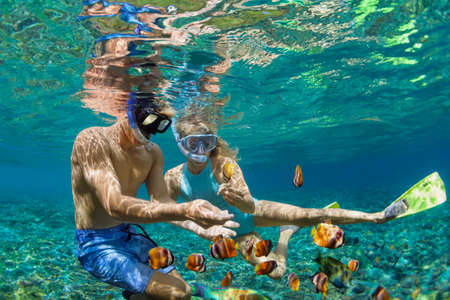 Happy family vacation. Young couple in snorkeling mask hold hand, dive underwater with fishes in coral reef sea pool. Travel lifestyle, watersport adventure, swim activity on summer beach holiday