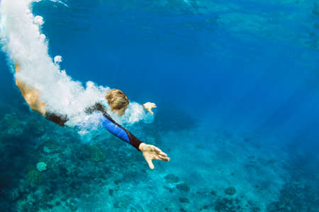 Happy family - active teenage girl jump and dive underwater in tropical coral reef pool. Travel lifestyle, water sport, snorkeling adventure. Swimming lessons on summer sea beach vacation with kids