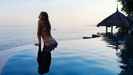 Happy girl enjoy on summer beach holiday. Young woman relaxing at edge of infinity swimming pool with sea view from hill top. Family cruise lifestyle, summer travel with kids on tropical islands.