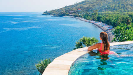 Happy girl have fun on summer beach holiday. Young woman relaxing at edge of infinity swimming pool with sea view from hill top. Healthy family lifestyle, summer travel with kids on tropical islands.
