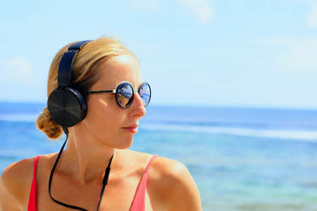 Young positive girl in headphones and sunglasses listening music and relaxing. Woman chilling at tropical sea beach. Travel family lifestyle, recreational activities at summer cruise vacations.