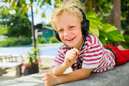 Young positive child in headphones listening music with fun at tropical beach party. Travel family lifestyle, recreational activities at summer cruise vacations. 免版税图像 - 150645563