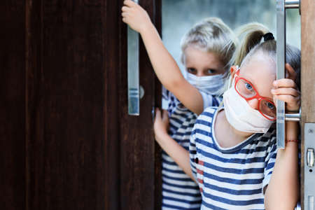 Little children looking unhappy and depressed after staying at home due banned street activity. Kids wearing medical face masks go out for outside walk, ending coronavirus Covid-19 disease quarantine. 版權商用圖片