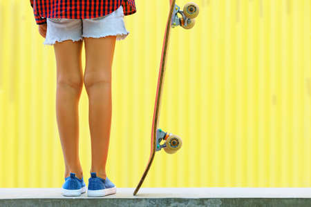 Young skateboarder girl in skate park. Close up view of legs, sneakers, skateboard. Active family lifestyle, outdoor activity on summer holidays in city. Kids sports and teenagers urban fashion.