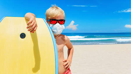 Young surfer wearing sunglasses, protective mask on sea beach with body board. Summer tours, cruises cancellation due to coronavirus COVID-19 epidemic.