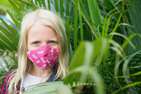 Portrait of child in funny protective mask. New rules to wear cloth face covering at public places. Cancelled cruise, tour due coronavirus COVID 19.