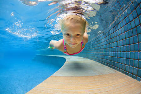 Funny portrait of child learning swimming, dive in blue pool with fun - jumping deep down underwater with splashes. Healthy family lifestyle, kids water sports activity, swimming lesson with parents.