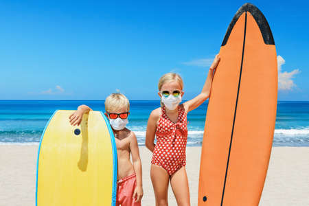 Funny kids with surf boards wear protective mask on sea beach. Cancelled cruises, tours due coronavirus COVID 19 world epidemic. Travel ban for family vacation, tourism industry crisis at summer 2020