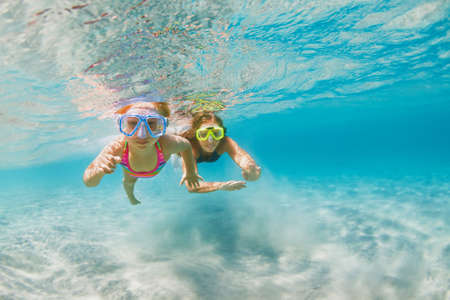Young mother with child in snorkeling mask dive in coral reef sea lagoon to explore underwater world.