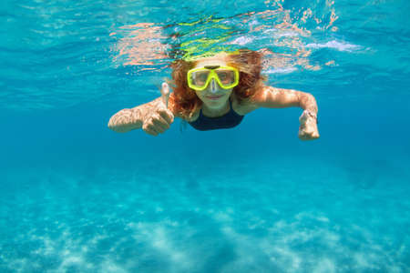 Young girl in snorkeling mask dive in coral reef sea lagoon to explore underwater world. Stock Photo