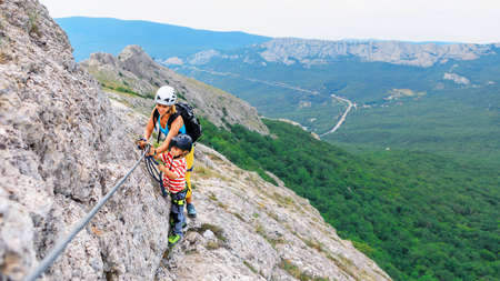 Young mother, child in safety equipment climb to mount top by via ferrata beginner route.