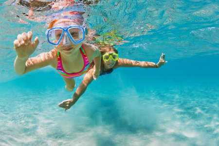Young mother with child in snorkeling mask dive in coral reef sea lagoon to explore underwater world. Family travel lifestyle in summer adventure camp. Swimming activities on beach vacation with kids. Banque d'images