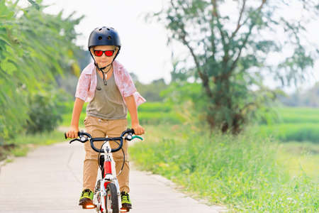 Country cycling walk. Young rider kid in helmet and sunglasses riding bicycle. Happy child have fun on empty trail. Active family lifestyle, sports, outdoor recreational activities on summer holidays.