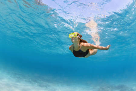 Young girl in snorkeling mask dive in coral reef sea lagoon to explore underwater world. Family travel lifestyle in summer adventure camp. Swimming activities on beach vacation with kids.