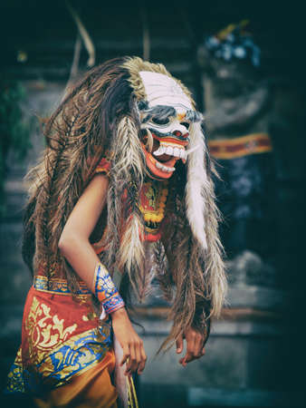 Dancer in demon Rangda traditional mask - evil spirit of Bali isalnd. Temple ritual dance at ceremony before Balinese silence day Nyepi. Religious festivals, art, ethnic culture of Indonesian people.