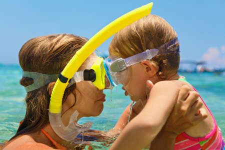 Happy family - mother, baby girl in snorkeling masks on sea beach of tropical island. Funny underwater swimming lesson. Travel adventure, swimming activity on summer holiday cruise with kids.