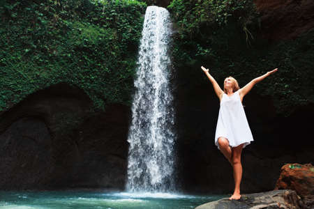 Young woman travel in Bali rainforest. Happy girl enjoy jungle nature. Stand in natural pool under waterfall, see on falling water. Walking day tour, hiking activity adventure on family summer holiday Banco de Imagens