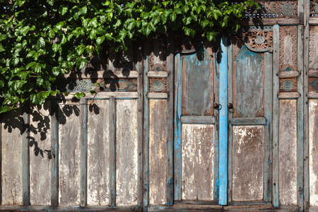 Locked wooden front door of traditional old house in Bali island, Indonesia. Banco de Imagens