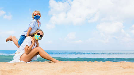 Mother, child in masks have fun on sea beach. New rules to wear cloth face covering at public places. Cancelled cruise, tour due coronavirus COVID 19. Family vacation, travel lifestyle at summer 2020 Foto de archivo - 159008635
