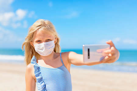 Funny girl taking selfie photo by smartphone on tropical sea beach. New rules to wear cloth face covering mask at public places due coronavirus COVID 19. Family holidays with children, summer travel. 版權商用圖片