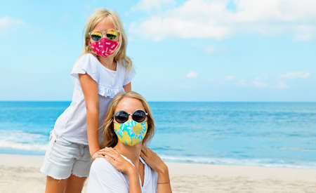 Mother, child in stylish masks have fun on sea sand beach. New rules to wear face covering at public places. Cancelled cruise, tour due coronavirus COVID 19. Family summer vacation, travel lifestyle.