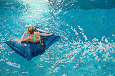 Top view of young baby girl on floating bean bag relaxing in blue swimming pool. Happy family travel background. Healthy lifestyle on summer beach holiday in luxury spa hotel.