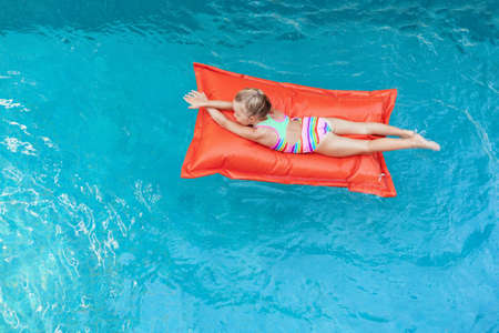 Top view of young baby girl on floating bean bag relaxing in blue swimming pool.
