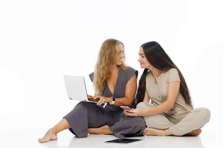 Young attractive women sit on floor, working on laptop, tablet computer and smarthphone. Two blogger girls write the text to internet blog. Teamwork and problem solving
