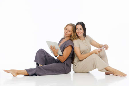 Young attractive women sit on floor, working on tablet computer and smarthphone. Two blogger girls write the text to internet blog. Teamwork and problem solving