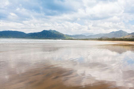 Red island beach ( pantai Pulau merah ) in Banyuwangi in Indonesia. Sky reflection in water pool at empty of people endless sand beach. East Java popular travel destination. Summer holiday background.