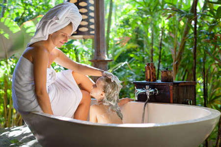 Happy baby girl, mother have fun in bath. Young woman soaping by shampoo child head in outside bathroom on open veranda with beautiful tropical garden viewing  luxury villa on summer family holiday Foto de archivo