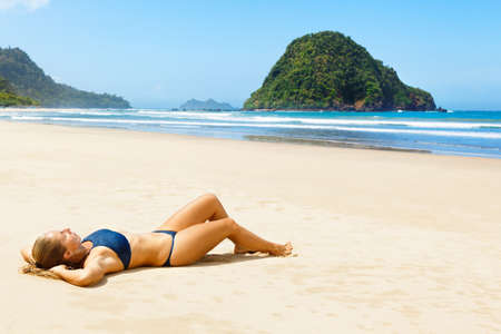 Happy young woman relax on tropical sand beach. Red island beach, pantai Pulau merah, Banyuwangi, east Java, Indonesia. Popular travel destination in Asia. Summer vacation lifestyle