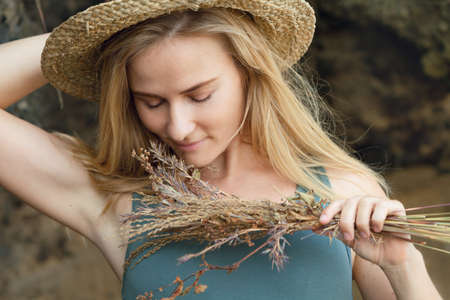 Young beautiful hipster woman in straw hat hold in hands bouquet of dried wild flowers. Happy romantic girl walk on tropical sea beach. Travel lifestyle, summer vacation accessories trend - boho style Foto de archivo