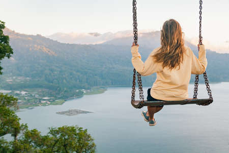 Summer vacation. Young woman sit on tree rope swing on high cliff above tropical lake. Happy girl looking at amazing jungle view. Buyan lake is popular travel destinations in Bali island, Indonesia