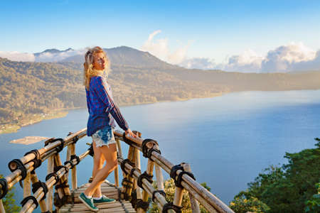 Summer family vacation. Young woman stand at balcony on high cliff. Happy girl looking at amazing tropical jungle view. Buyan lake is popular travel destinations in Bali island, Indonesia Foto de archivo