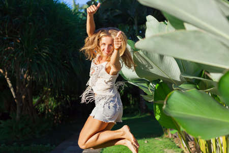 Happy young woman have fun on tropical resort. In luxury villa garden funny girl jumping high show thumbs up. Active lifestyle, people travel activity on summer family holiday. Foto de archivo