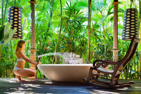 Happy young woman have fun in open air bathtub. Joyful girl take bath in outside bathroom on veranda with beautiful tropical garden view in luxury villa on summer family vacation.