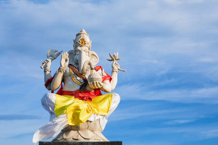 Ganesha sitting in meditating yoga pose in front of hindu temple. Decorated for religious festival by colorful cloth, ceremonial offering. Balinese travel background. Bali island art, culture.