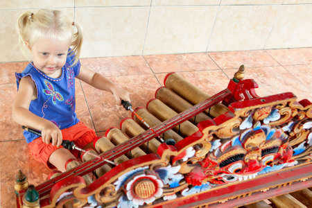 Little funny child play music on traditional indonesian musical instrument - bamboo xylophone Rindik or Tingklik. Arts, culture of Bali island and Indonesia.