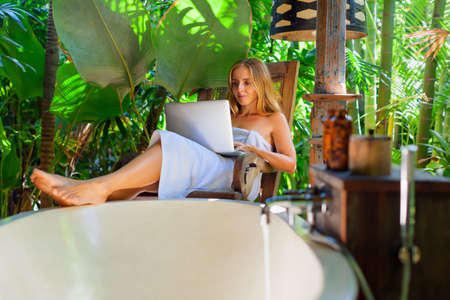 Freelance blogger sit at wood chair, work on laptop computer, type text for travel blog. Relaxing woman fill bath tub in vintage style outside bathroom in luxury villa on summer tropical vacation.