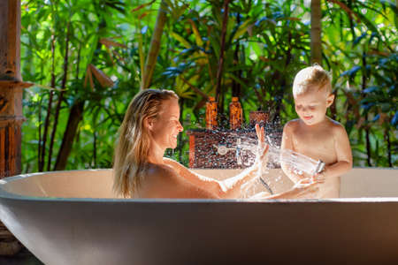 Happy baby son with mother have fun in bath. Playful woman spraying child from shower in outside bathroom on open veranda with beautiful tropical garden view in luxury villa on summer family vacation. Foto de archivo