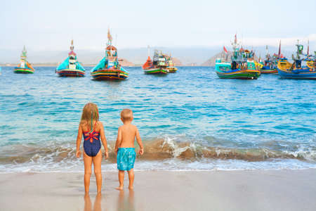 Happy family - kids walk along sea surf on sand beach, look at traditional fisher boats. Pantai Tanjung Papuma, Jamber, Java, Indonesia. Popular travel destination. Summer vacation with kids.