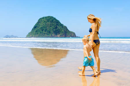 Happy family - mother, baby son have fun, walk by water pool along sea surf on sand beach. Red island beach, pantai Pulau merah, Java, Indonesia. Popular travel destination. Summer vacation with kids.