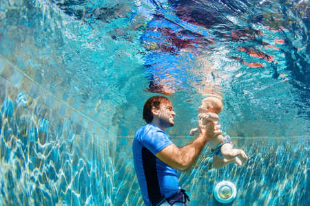 Happy people dive underwater with fun. Funny photo of father, child in aqua park swimming pool. Family lifestyle, kids water sports activity, swimming lesson with parents on summer holiday Foto de archivo