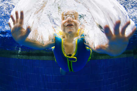 Funny portrait of child learning swimming, dive in blue pool with fun - jumping deep down underwater with splashes. Healthy family lifestyle, kids water sports activity, swimming lesson with parents. Foto de archivo