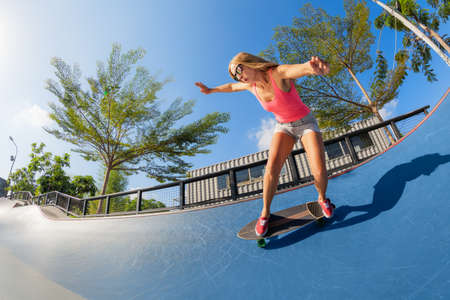 Skateboarder in action. Young woman making trick on surf skate longboard in outdoor skatepark bowl. Surfskate and skateboard riding lessons at summer sport camp. Teens weekend recreational activities.