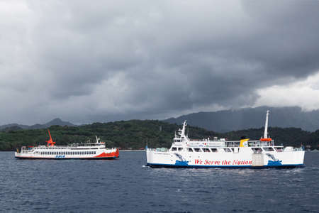 Padang Bay, Bali island, Indonesia - July 10, 2017: Oncoming ferry traffic between Bali, Lombok, Nusa Penida. Public transport and transportation of goods by sea between islands in Indonesia