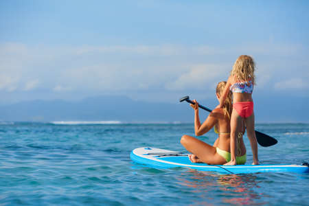 Active paddle boarder at sunset sea. Young mother with little clild paddling on stand up paddleboard. Healthy lifestyle. Water sport, SUP surfing tour in adventure camp on family summer beach vacation Foto de archivo