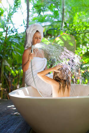 Happy baby girl with mother have fun in bath. Playful woman spraying child from shower in outside bathroom on open veranda with beautiful tropical garden view in luxury villa on summer family vacation Foto de archivo