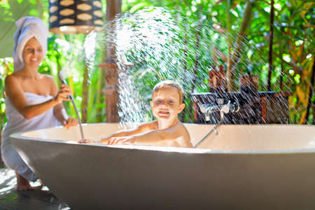 Happy baby boy with mother have fun in bath. Playful woman spraying child from shower in outside bathroom on open veranda with beautiful tropical garden view in luxury villa on summer family vacation Foto de archivo